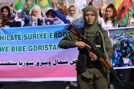 Kurdien turvallisuusjoukkoihin kuuluva nainen valvoi kurdien mielenosoitusta pohjoissyyrialaisessa Hasakan kaupungissa lauantaina.