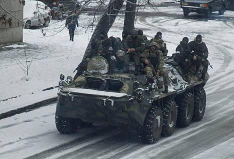 Aseistautuneita miehiä panssaroidun miehistönkuljetusajoneuvon kyydissä Luhanskissa torstaina.