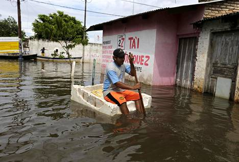 Mies kulki lautan päällä Paraguayn pääkaupungissa Asunciónissa joulukuussa 2015 tulvien noustua kaupungin kaduille.