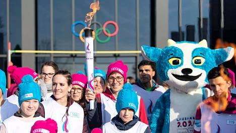 Nuorten talviolympialaiset alkavat Sveitsin Lausannessa torstaina. Ryhmä soihdunkantajia poseerasi keskiviikkona kisamaskotin kanssa olympiamuseon edustalla. Soihtua kantava urheilija on sveitsiläinen maastopyöräilijä Linda Indergrand.