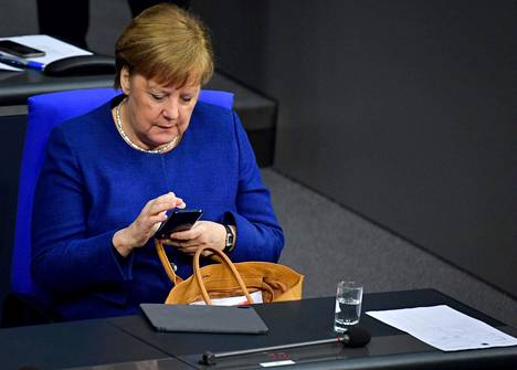 Angela Merkel katsoi matkapuhelimeensa vieraillessaan Saksan parlamentissa 6. maaliskuuta. Nyt Saksa uhkaa Venäjää uusilla pakotteilla, koska se katsoo Venäjän olleen todistetusti vuoden 2015 suuren tietosuojahyökkäyksen takana.