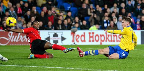 Arsenalin Aaron Ramsey (oik.) laukoo joukkueensa kolmannen maalin Cardiffin verkkoon Englannin Valioliigan ottelussa lauantaina.
