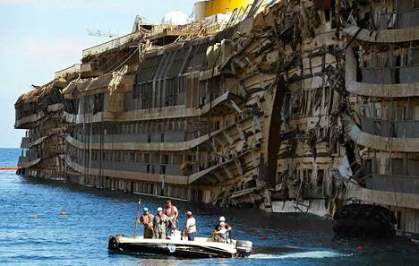 Costa Concordia ajoi kaksi vuotta sitten karille Italian luoteisrannikolla. Kyljellään vedessä maannut laiva saatiin pystyyn vasta syyskuussa.