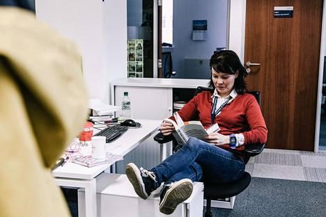 """Tohtori Mari K. Niemi suosikkilukuasennossaan työpöytänsä ääressä. """"Populismistakin löytyy hyvää, jos se tarkoittaa sitä, että sivuun jääneet saavat äänensä kuuluviin."""""""