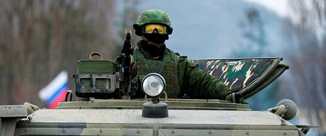 Venäläissotilas tähyili panssariajoneuvostaan ukrainalaisen sotilastukikohdan edustalla Krimin Simferopolissa tiistaina.