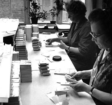 Pelikorttien lajittelu on tarkkaa työtä. Valmiiseen pakkaan ei saa päästä yhtään virheellistä korttia. Pakkausvaiheessa kiinnittävät rouvat Eija Lahdelma (oik.) ja Alli Kyöstilä myös veronauhat korttien ympärille.