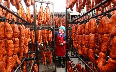 Työntekijä ripusti makkaroita ja pekonia lihatehtaassa Sichuanin maakunnassa Kiinassa viime joulukuussa.