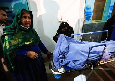 Sukulaisia ammutun naistoimittajan ruumiin ympärillä sairaalassa Jalalabadin kaupungissa Afganistanissa maaliskuun alussa.