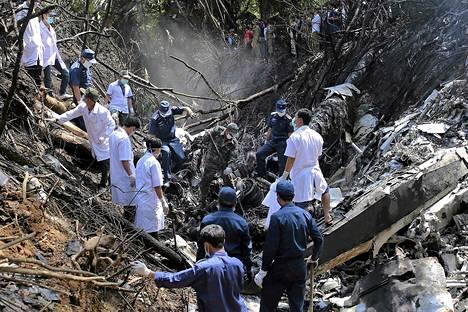 Pelastustyöntekijät tutkivat lentokoneen putoamispaikkaa Laosissa lauantaina.