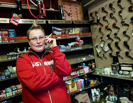Myyjä Päivä Sulinko poltteli helsinkiläisessä tupakkakaupassa torstaina. Hän harmittelee yleisten tupakkasäännösten kiristymistä ja pienten erikoisliikkeiden kuihtumista.
