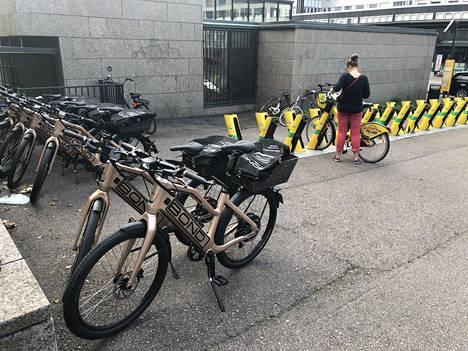 Sähkökaupunkipyörien kypärä kulkee mukana takatelineellä. Pyöriä on viety muun muassa Kampin metroaseman viereen.