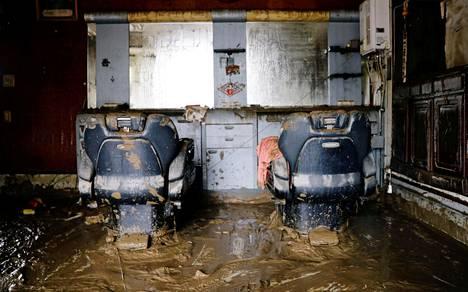 Rankkasateista johtuva mutavyöry täytti parturiliikkeen lattian liejulla. Rankkasateet ovat aiheuttaneet valtavaa tuhoa japanilaisissa kaupungeissa.