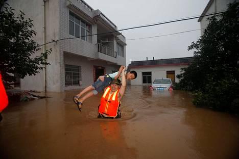 Pelastustyöntekijä kantoi lasta tulvaveden valtaamassa Wuhanin kaupungissa Kiinassa heinäkuussa 2016. Kaupunki on nimennyt itsensä pesusienikaupungiksi ja ottanut käyttöön muun muassa vettä imevän asfaltin.