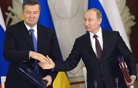 Venäjän presidentti Vladimir Putin (oik.) ja hänen ukrainalainen virkaveljensä Viktor Janukovytš kättelivät sopimuksen merkiksi tiistaina Moskovassa.