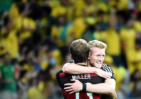 Andre Schürrle (oik.) sai Thomas Mülleriltä onnittelut maalistaan Saksan suurvoitossa Brasiliaa vastaan.