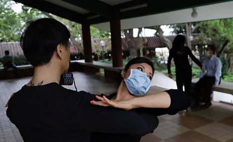 Tanssinopettaja (vas.) tanssitti kasvomaskilla varustautunutta oppilastaan hongkongilaisessa puistossa pidetyllä tanssitunnilla huhtikuussa.