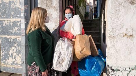 Huonokuntoisessa vuokratalossa Portossa asuva portugalilainen Patricia Ferreira (oik.) sai avustusjärjestön vapaaehtoiselta Isabel Brandãolta täkkejä ja pipoja karkottamaan talvista koleutta. Ferreira ei kykene maksamaan kotinsa lämmityskuluja.