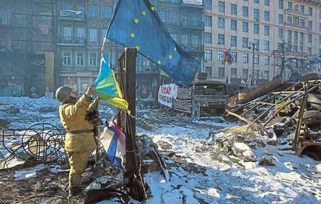 Ukrainan hallintoa vastustanut mielenosoittaja kiinnitti Ukrainan ja Euroopan unionin lippuja barrikadiin Kiovassa helmikuun alussa 2014.