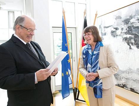 Saksan suurlähettiläs Dorothee Janetzke-Wenzel ojensi kansalaisasiakirjat Pertti Hartikaiselle, jolla on nyt kaksoiskansalaisuus.