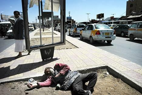 Mies makaa kadulla Sanaassa. Kuva otettu vuonna 2010.