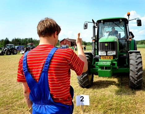 Ilja Saveljev näyttää taktisia käsimerkkejä traktorin ratissa istuvalle Vladislav Poljakoville. Saveljev on ensimmäistä kertaa ulkomailla. Hän ei ole aiemmin ajanut muita traktoreita kuin Belaruksia.