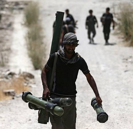 Syyrian kapinallisiin kuuluva sotilas kantoi aseistusta etulinjaan.