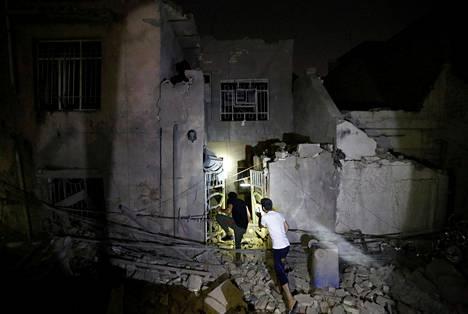 Ihmiset tutkimassa räjähdyspaikkaa Bagdadissa.