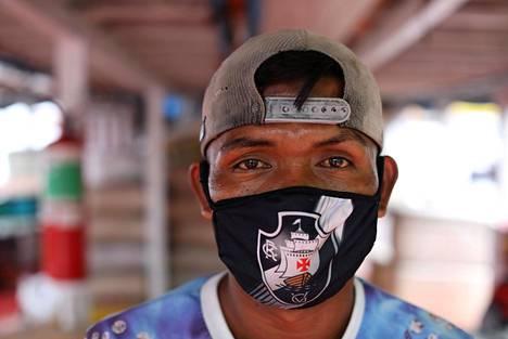 Brasilialaismies suojasi kasvonsa Manauksen satamassa kasvonsa maskilla, jota koristi jalkapalloseura Vasco Da Gaman logo.