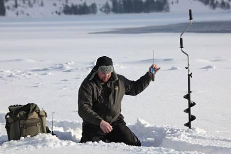Mies pilkki lohikalaa Tikkasenkarilla Kemijoella helmikuussa 2011.