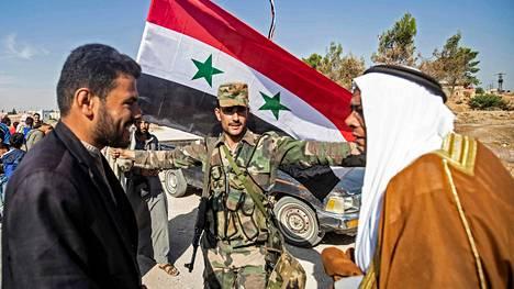 Ihmiset toivottavat syyrialaisjoukot tervetulleiksi Tal Tamrin kaupungissa Koillis-Syyriassa lähellä Turkin rajaa.