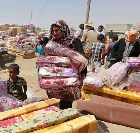 Kotinsa jättänyt irakilaisnainen keräsi avustustyöntekijöiden jakamia tyynyjä ja patjoja Aski Kalakin väliaikaisella pakolaisleirillä Mosulin itäpuolella Pohjois-Irakissa.