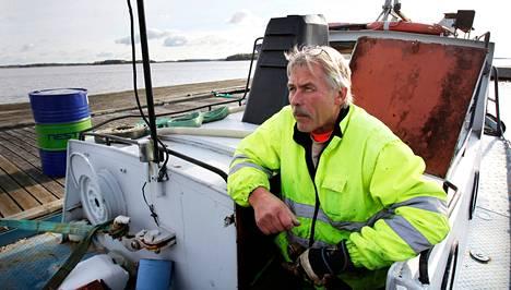 Monitoimimies Lasse Saarivuori huoltaa hinaajaa Taivassalon Hakkenpään entisen sahan laiturissa.