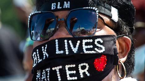 Rasisminvastaiseen marssiin osallistunut oli pukenut päällleen Black Lives Matter -iskulausetta kantavan kasvosuojan.