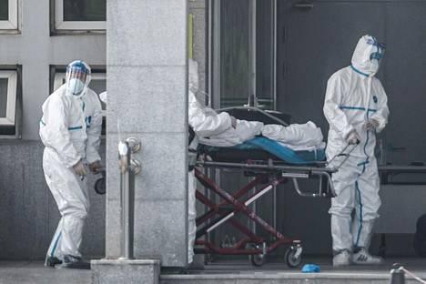 Työntekijät kuljettivat lauantaina potilasta Hubein pääkapungissa Wuhanissa sijaitsevaan Jinyintan-sairaalaan, jossa hoidetaan koronavirustartunnan saaneita ihmisiä.