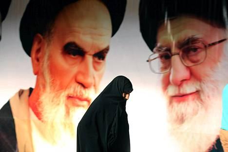 Iranilaisnainen käveli ajatolla Khomeinia (vas.) ja hänen seuraajaansa Ali Khameneita esittävän julisteen ohi Teheranissa helmikuun alussa.