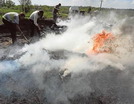 Venäjän-mieliset aktivistit yrittivät sammuttaa palamaan syttynyttä barrikadia lähellä Itä-Ukrainan Slovjanskia sunnuntaina.