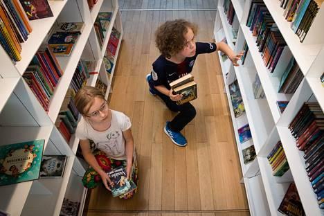 Lovisa Naulapää (vas.) ja Vilho Toppinen koluavat Helsingin keskustakirjaston Oodin hyllyjä.