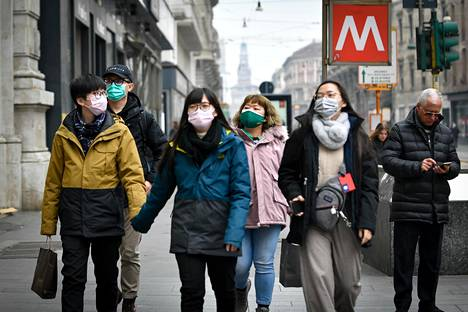 Ihmiset käyttivät hengityssuojaimia kulkiessaan Milanossa tiistaina.