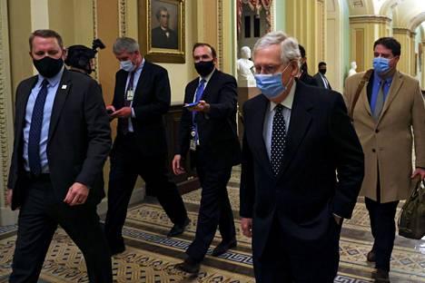 Republikaanijohtaja Mitch McConnell (oik.) poistui kongressitalosta presidentinvaalin ääntenvahvistuksen jälkeen torstaina.