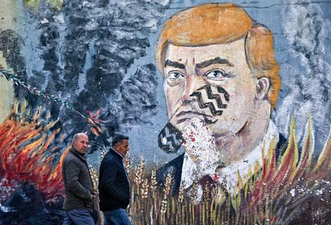Palestiinalaismiehet kävelivät Donald Trumpia esittävän seinämaalauksen ohi Gazassa tiistaina. Kasvojen päällä oleva kengänjälki osoittaa halveksuntaa.