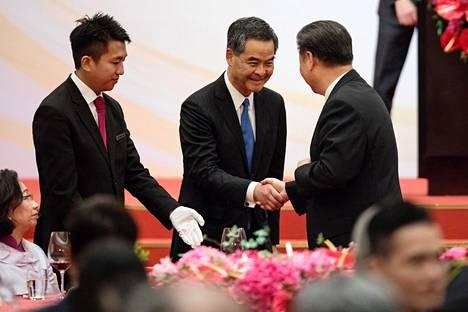 Hongkongin edellinen hallintojohtaja Leung Chun-ying (kesk.) ja Kiinan presidentti Xi Jinping (oik.) kättelivät kesällä 2017.