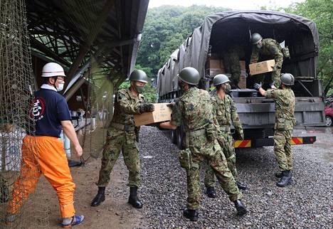 Japanin puolustusvoimien jäsenet purkamassa avustustarvikkeita Kumamuran kylässä torstaina. Kumamoton prefektuuri kärsi pahoin tulvan aiheuttamista vahingoista.