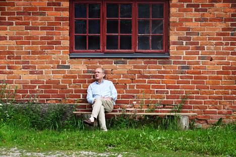 Antti Herlin istuu vanhan tallin edessä kotonaan Kirkkonummen Thorsvikissä.