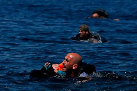 Syyriasta pakolaisena eurooppaan yrittänyt mies kannatteli lastaan merenpinnan yläpuolella Lesboksen saaren edustalla joulukuun alussa.