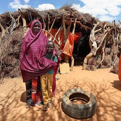 Rouva Deqa Ahmed ja poika Mohammed Omar kodin edustalla. Ahmed säännöstelee vesiauton tuomaa vettä niin, että perheessä kukin saa korkeintaan seitsemän desilitraa päivässä.