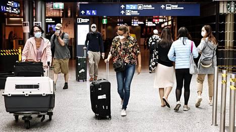 Matkustajat käyttivät suojamaskeja Helsinki-Vantaan lentokentällä maanantaina.