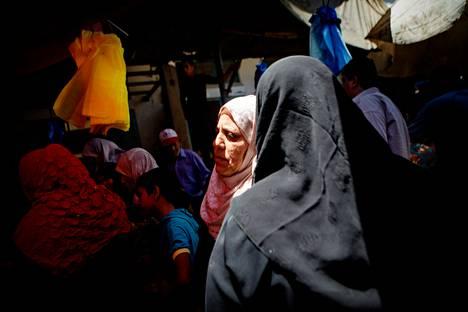 Gazan torilla oli ruuhkaa, kun ihmiset, muun muassa Banzeh Abu Zeina (valokiilassa), hakivat ruokatarpeita tulitauon aikana.