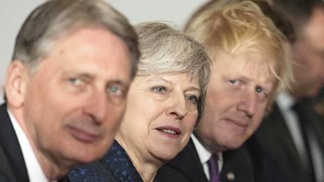 Kovan brexitin suosijat toivovat potkuja valtiovarainministeri Philip Hammondille (vas.). Hänen vierellään pääministeri Theresa May ja brexit-leirin kärkihahmoihin kuuluva ulkoministeri Boris Johnson. Kuva on otettu Sandhurstin sotakorkeakoulussa Britannia-Ranska-huippukokouksessa tammikuussa.