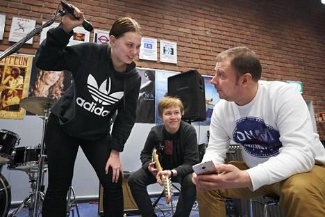 Munkkiniemen yhteiskoulun musiikkiryhmässä Whatsappissa sovitaan esimerkiksi harjoitusaikatauluja ja soitettavia kappaleita. Kuvassa vasemmalla on Saga Uusikylä, keskellä Mikko Koskinen ja oikealla musiikinopettaja Ville Sumelles.