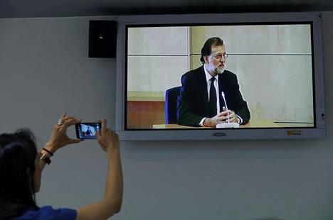 Toimittaja otti kuvan todistustaan antavasta Espanjan pääministeristä Mariano Rajoysta oikeudenkäynnin lehdistöhuoneen tv-ruudusta San Fernando de Henaresissa Madridin liepeillä.